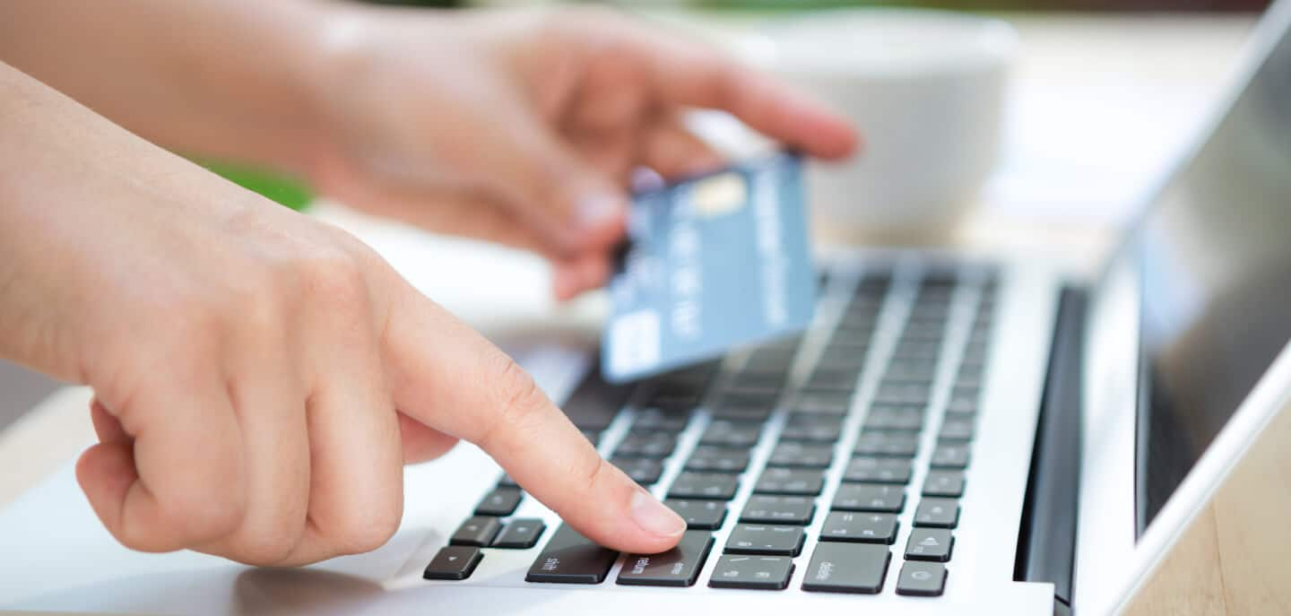 Recurring billing: Person typing credit card information to a laptop