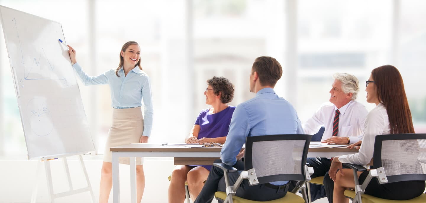 Woman presenting to 4 people in a business consulting meeting