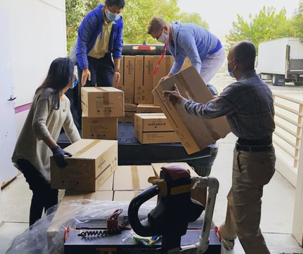 Four people moving boxes from a warehouse to a truck